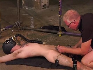 Mature dom hides subs face with gas mask as he jerks him off